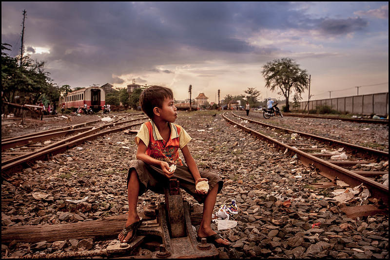 A boy eating in a train-truck slum in Phnom Penh, Cambodia. Source: Zoriah's flickr photostream, used under a creative commons license.