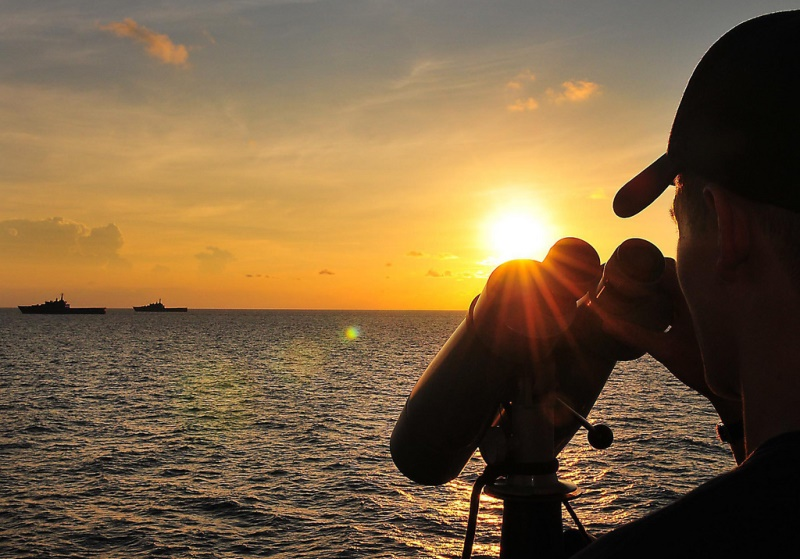 U.S. sailor stands watch in the South China Sea. The United States has made it explicitly clear that international law will be the sole basis for arbitration of disputes among claimants in East and Southeast Asia. Source: CARAT's flickr photostream, U.S. government work.
